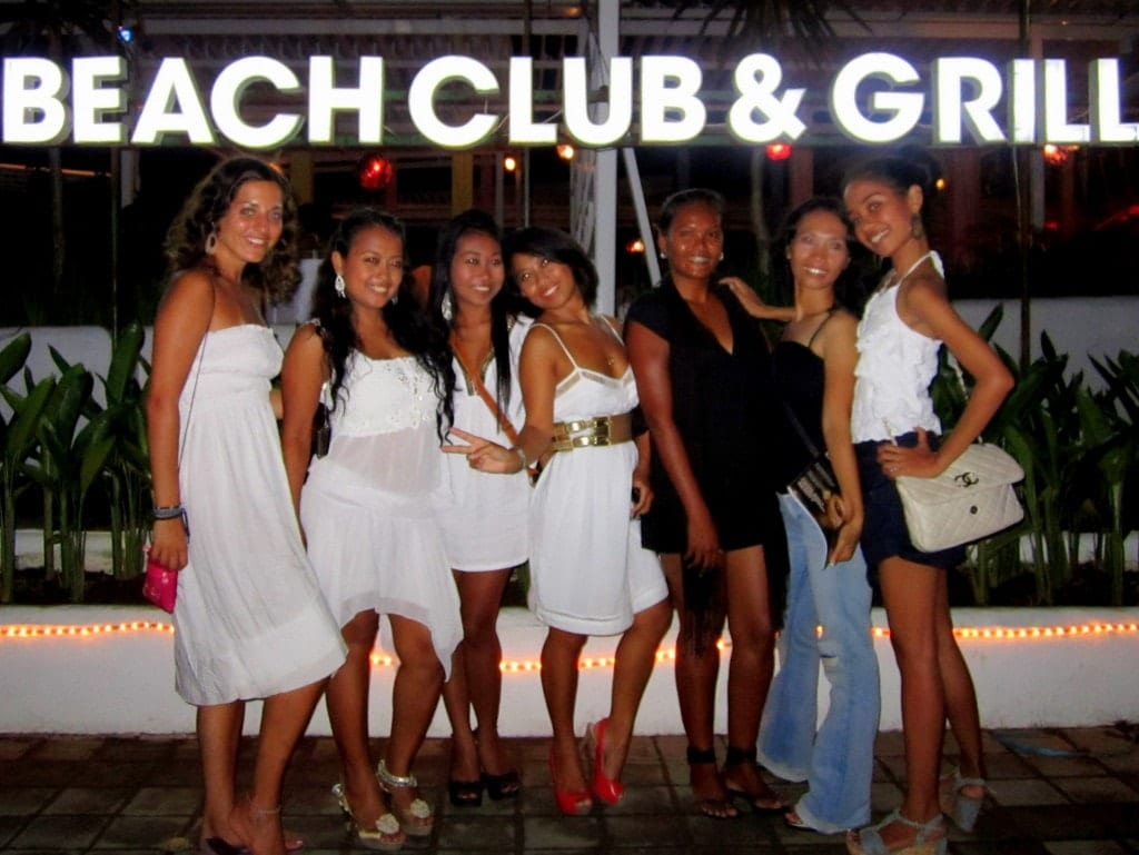 Kate and several Indonesian girlfriends, most dressed in white dresses, at a beach party labeled BEACH CLUB AND GRILL.