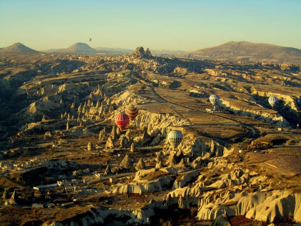 Hot air balloons flying over the jagged landscape of Cappadocia, Turkey.