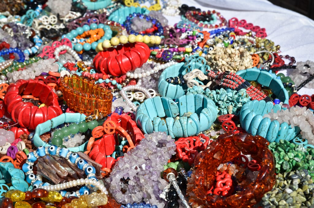 Plastic bracelets for sale, mostly red and turquoise, on a table in New York.