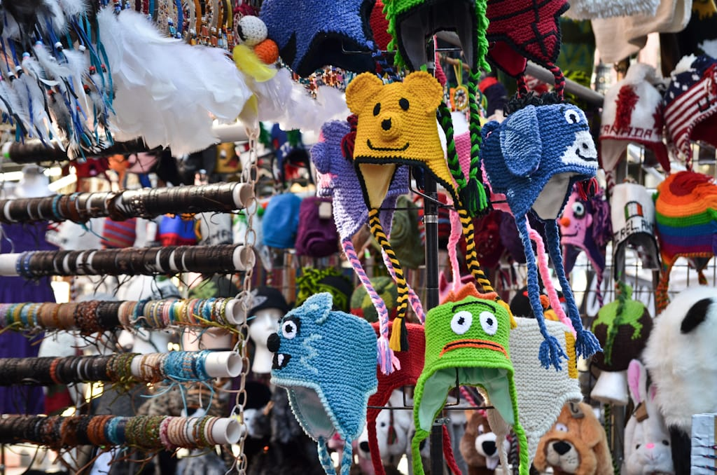 A market stall with lots of cartoon-y knit hats with goofy faces on them.