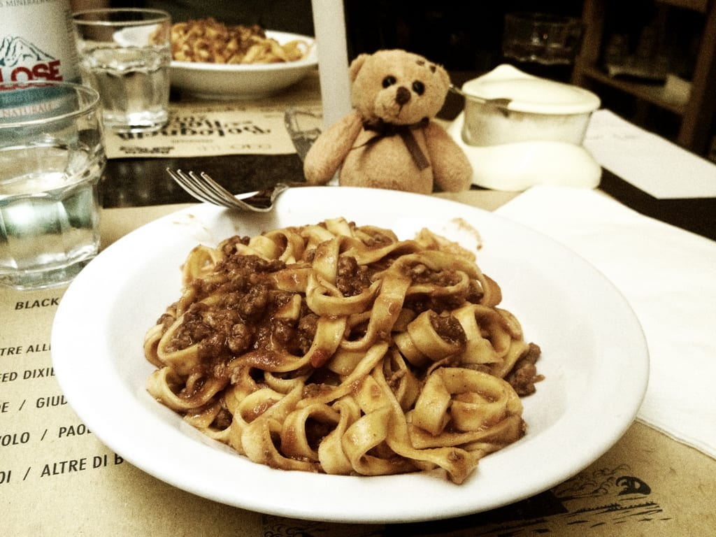 A bowl of tagliatelle ragu in Bologna, pasta with meat sauce, with a little teddy bear overlooking the plate.