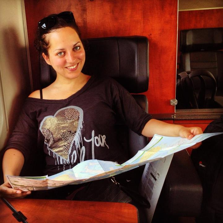 Kate holds a map while sitting on a train.