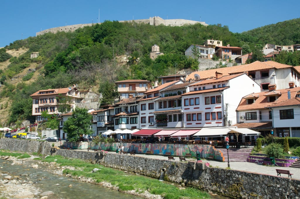 White houses with red roofs on the banks of a nearly-dry river in Prizren, Kosovo.