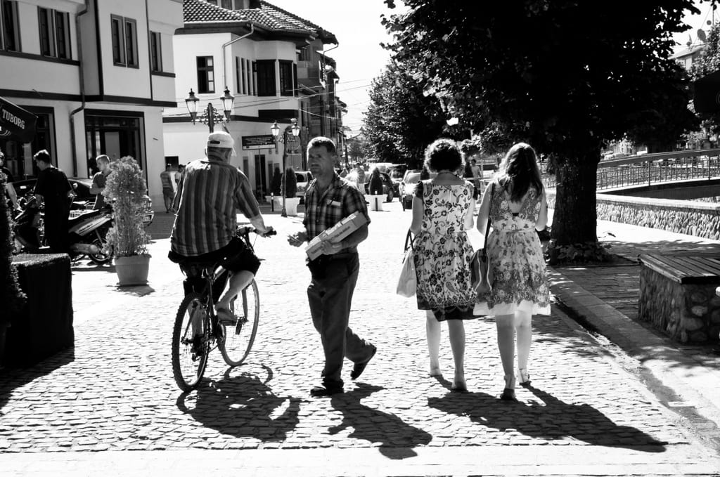 A black and white shot of people walking down the street in Prizren, Kosovo