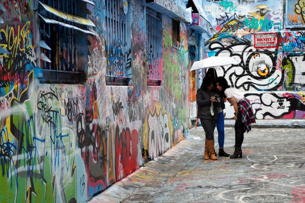 An alley filled with graffiti, with women under an umbrella looking at their phones.