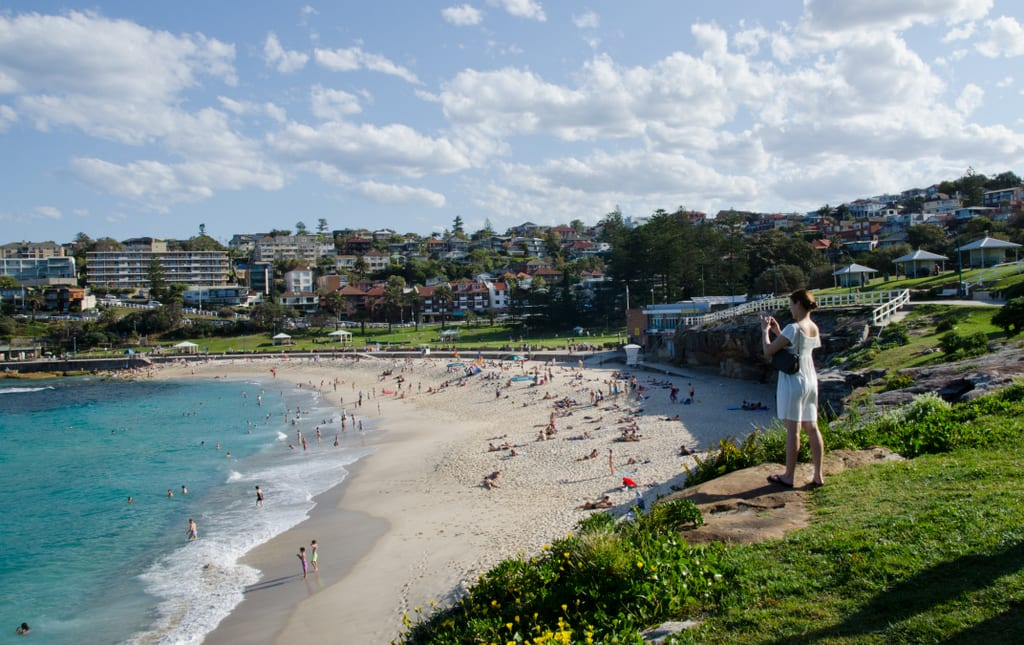 A woman in a white dress standing on a cliff and taking a picture of the beach in Bronte, Sydney. The water is bright turquoise and the sky is pale blue streaked with clouds.
