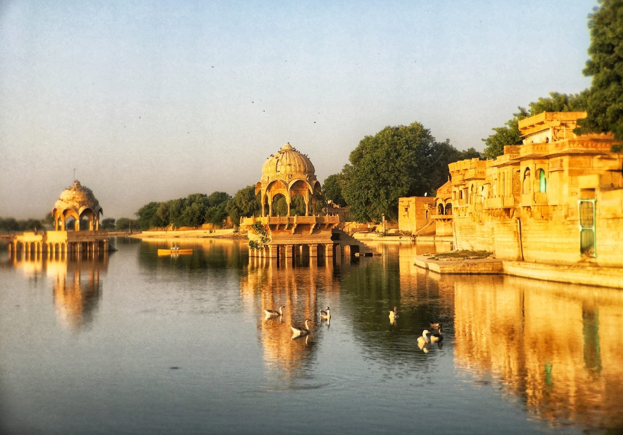 The golden buildings of Jaisalmer, Rajasthan, India, perched on the blue lake at dusk.