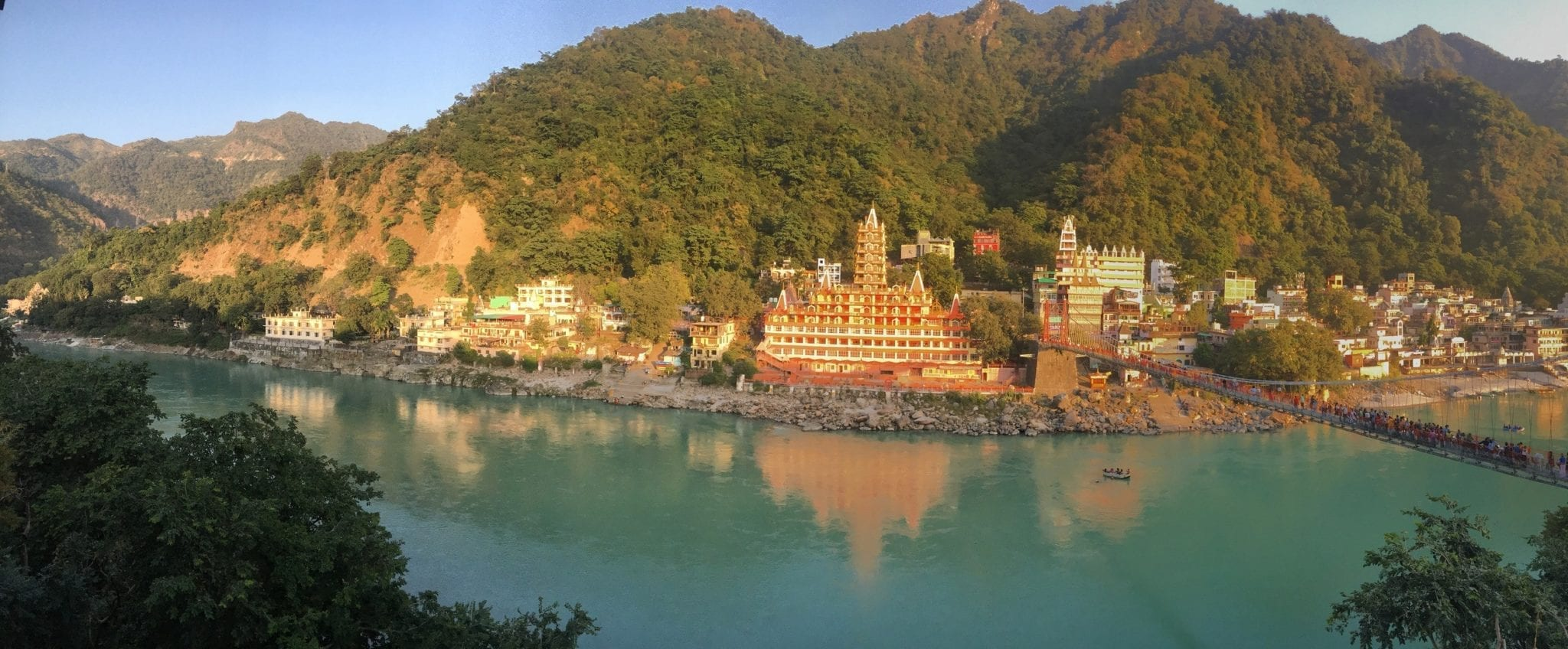 Orange temples nestled into green hills on a turquoise lake in Rishikesh, India.