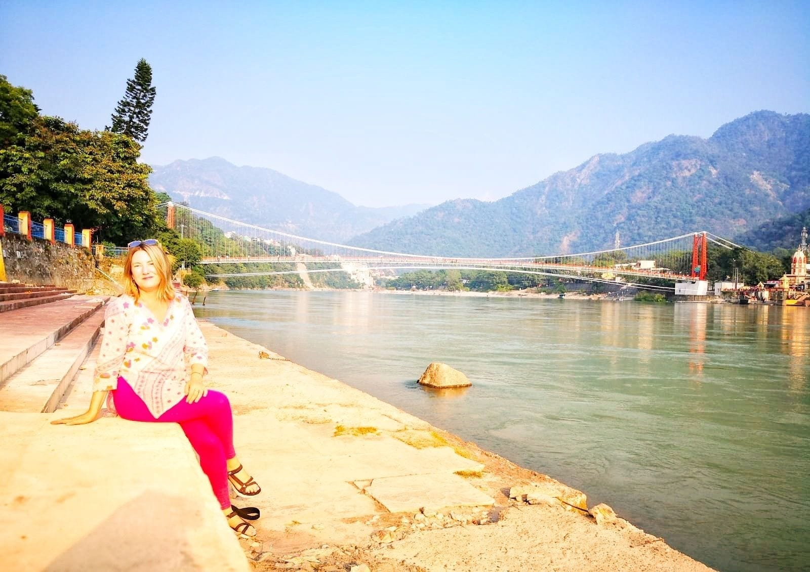 Mariellen Ward wears a white Indian top and pink trousers and poses on the banks of the Ganga river in Rishikesh, mountains behind her.