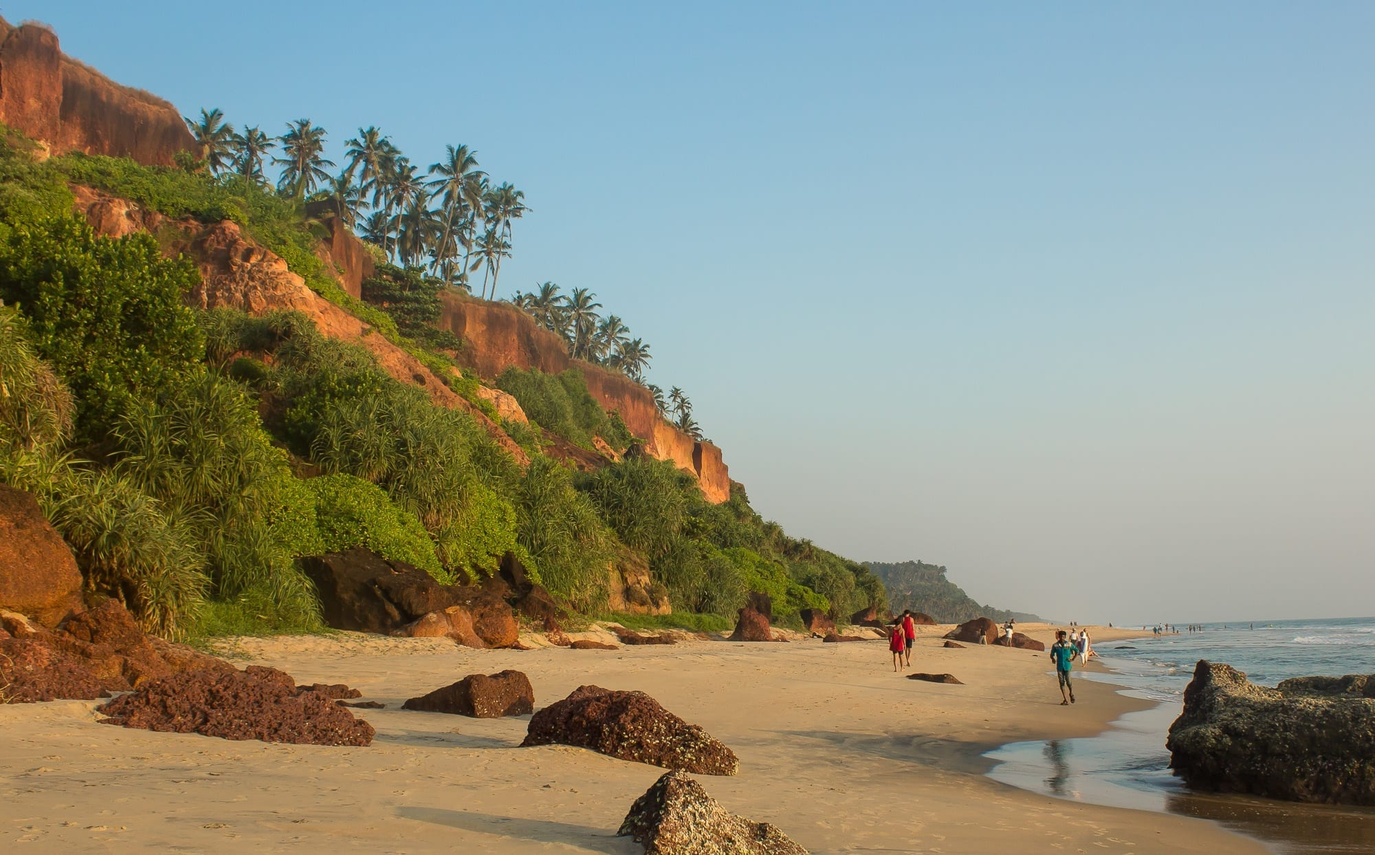 Cliffs and beach leading into the ocean in Varkala, Kerala, India, palm trees rising from the hills.