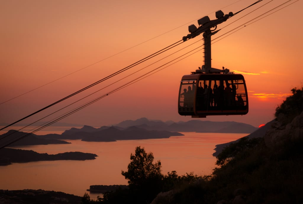 A cable car in Dubrovnik, silhouetted from behind during an orange sunset, islands in the distance.