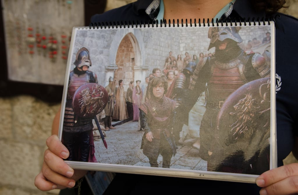 A set of hands in Dubrovnik holds a picture of a scene from Game of Thrones taking place in the Dubrovnik walls.