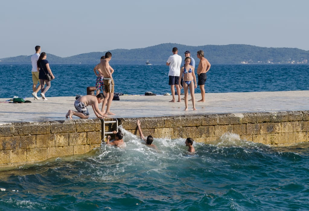 Boys swimming in the waves off a dock in Zadar, Croatia
