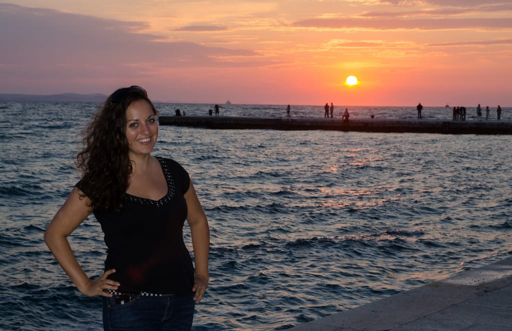 Kate poses in front of a sunset in Zadar, Croatia.