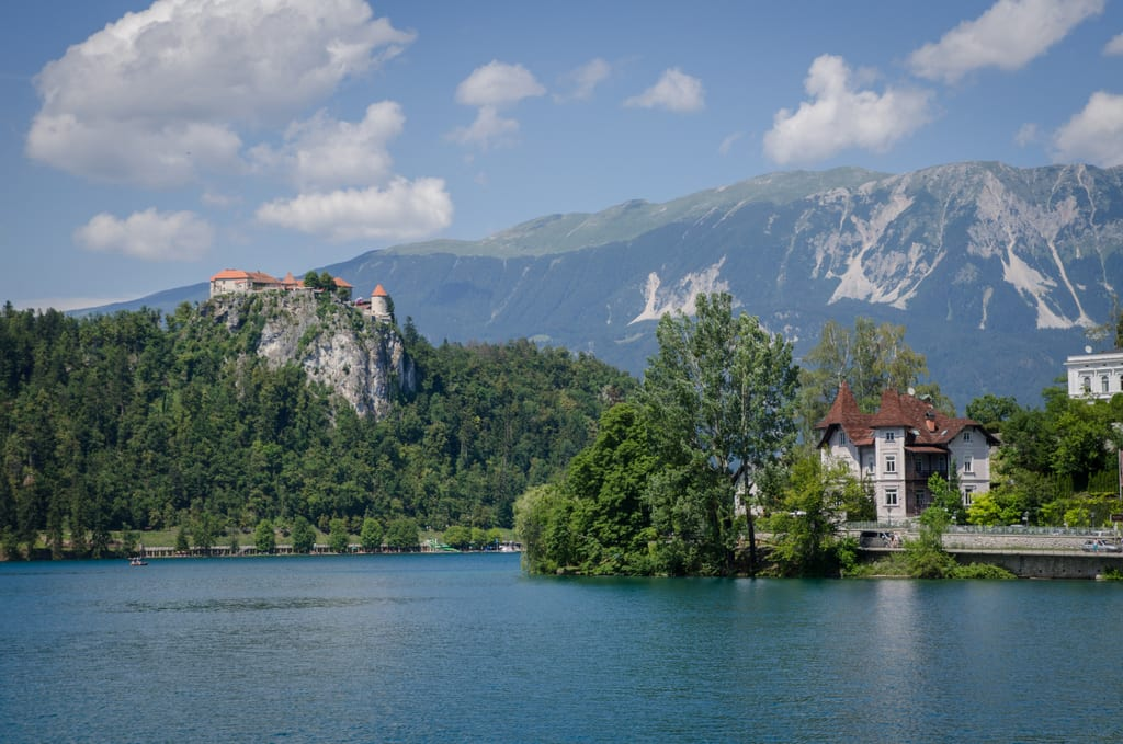 Lake Bled: a soft blue lake with mountains in the background. On the left is a castle perched on top of a cliff right next to the lake; on the right is a smaller white building in the foreground.
