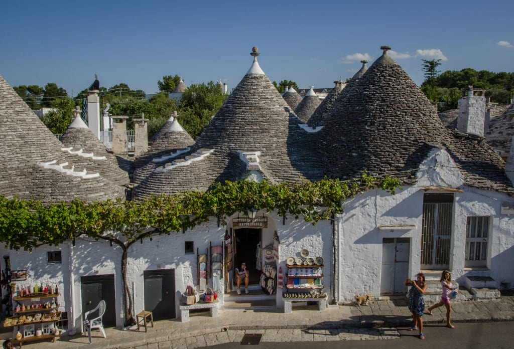 """White conical """"Trulli"""" homes in Alberobello, Italy. Several homes are stuck together with gray shingled pointy roofs. A tree grows alongside a wall. Several doors have gift shops and two women are taking pictures of the houses."""