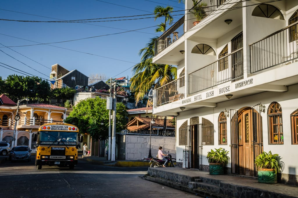 A bus and a white wooden hotel in San Juan Del Sur.