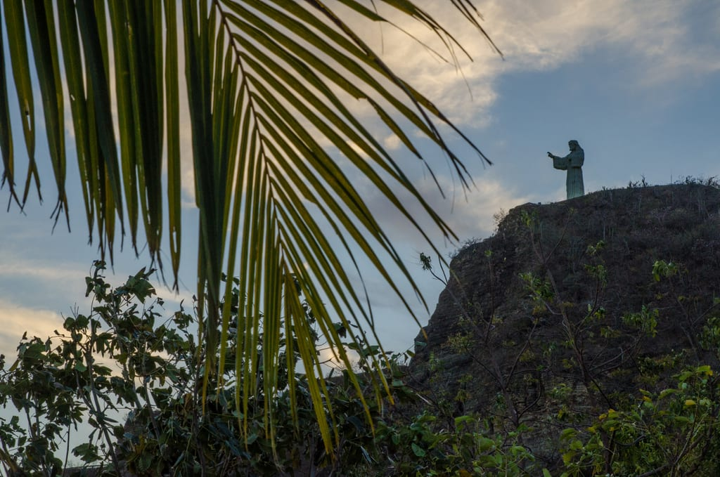 Jesus statue on a mountain in San Juan Del Sur, a palm frond in the foreground.