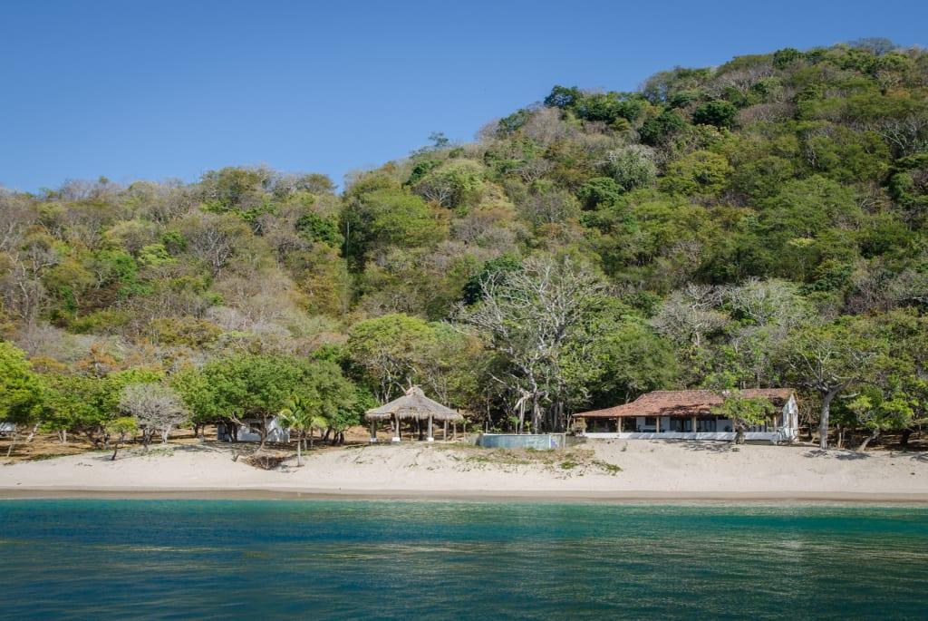 A beach near San Juan Del Sur, with still green water.