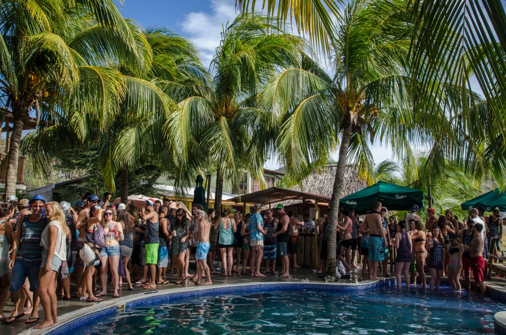 Partiers clustered around a pool, surrounded by palm trees, at Sunday Funday in San Juan del Sur, Nicaragua