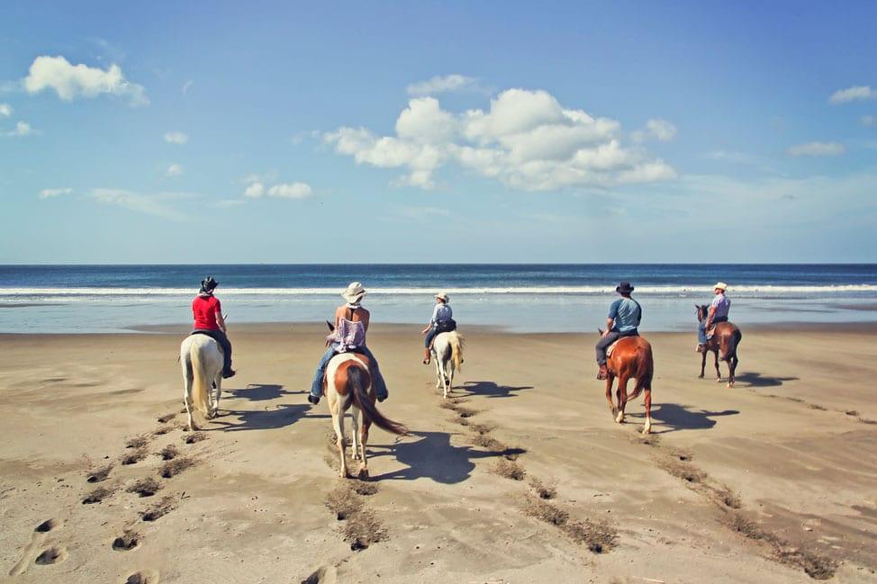 Five women on horseback on a beach, facing the sea.