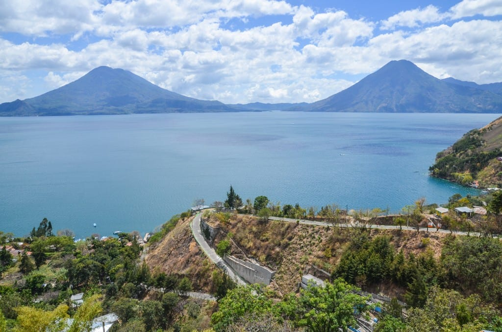 Curvy road on a cliff in front of Lake Atitlan, volcanoes in the background.
