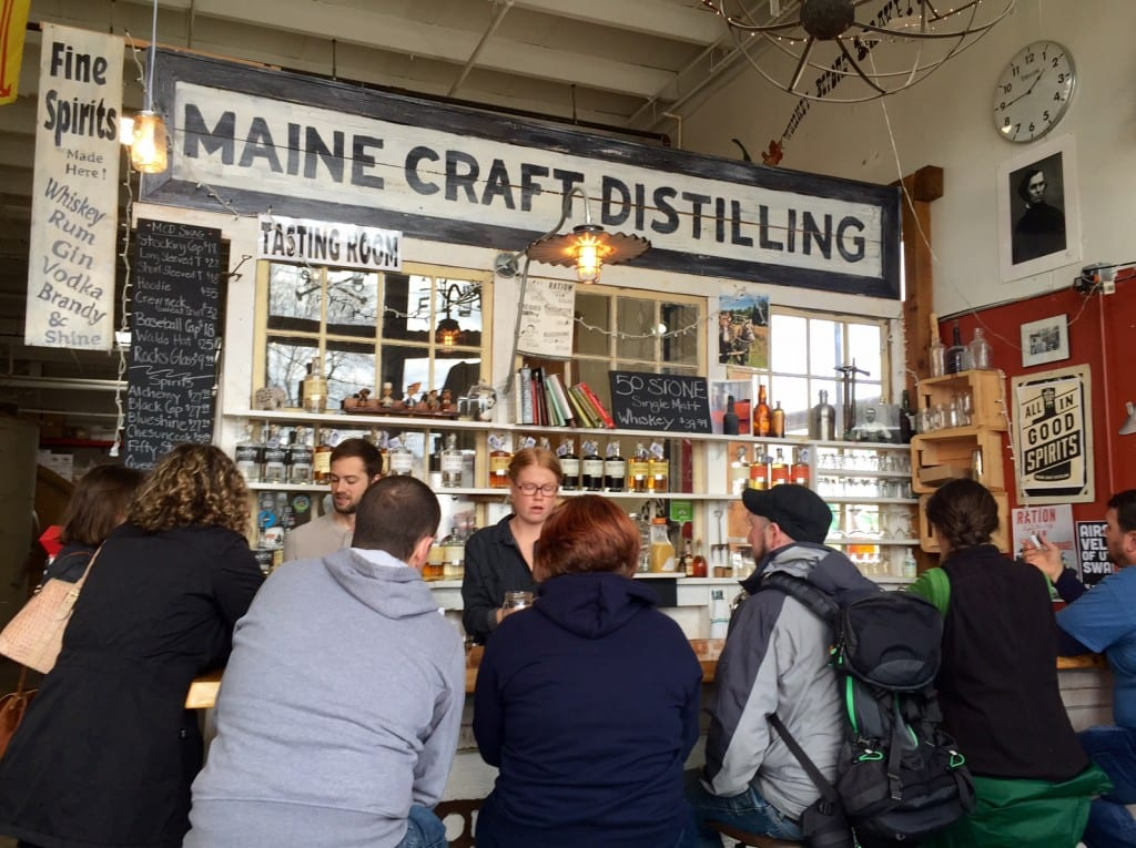 "Customers sitting at a tasting counter with ""Maine Craft Distilling"" written on a sign."