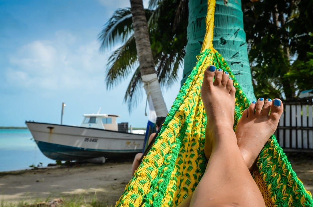 Feet in a green and yellow hammock with a boat on the beach in the background