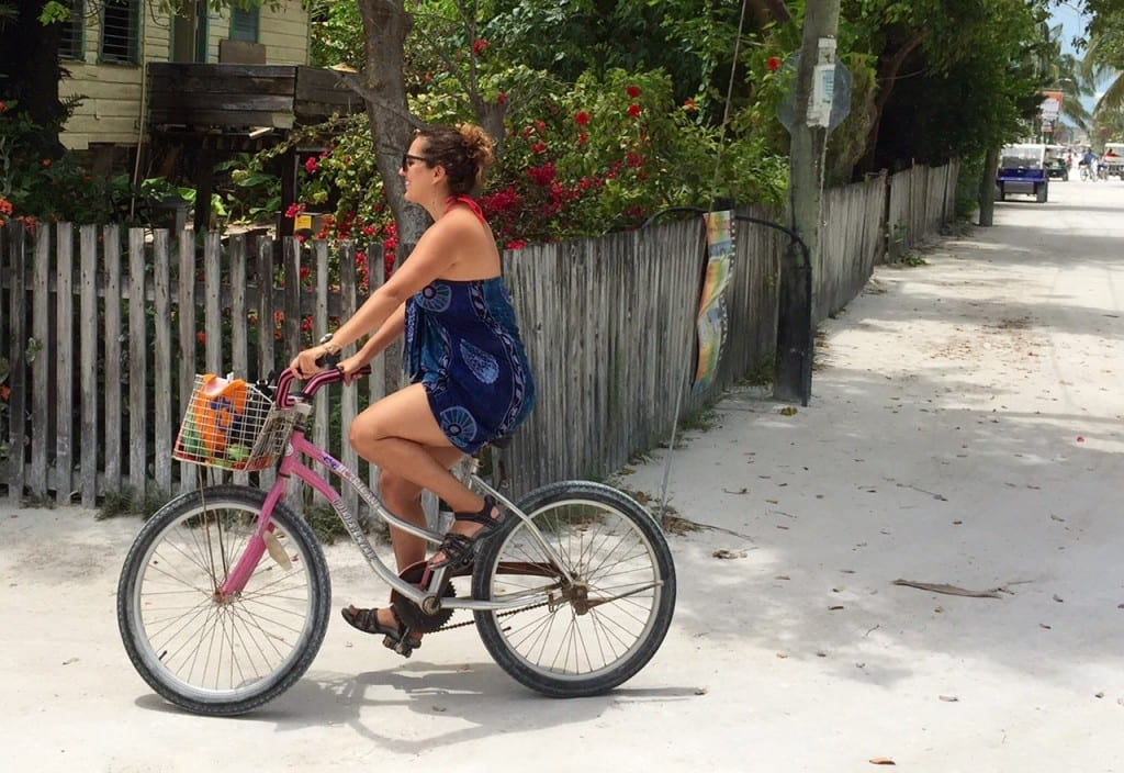 Kate rides a bike down a sandy road in Caye Caulker, Belize.