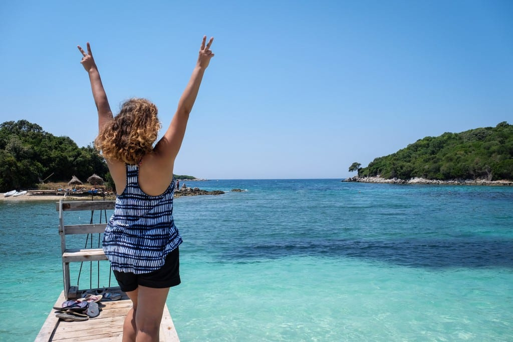 Kate faces away from the camera with her arms in the air in front of the turquoise water of Ksamil, Albania