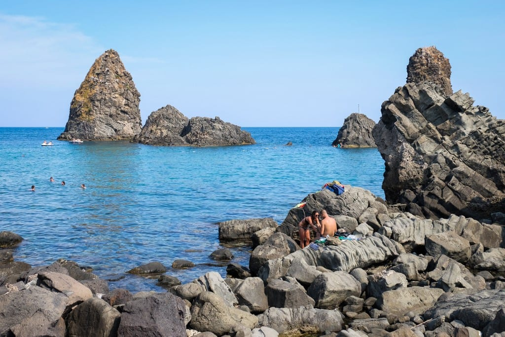 People sunbathing on the rocky coastline of Aci Trezza, Sicily, boulders in the water rising in the distance.