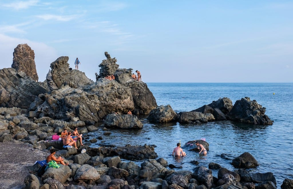 People hanging out on the rocky coastline in the blue water of Aci Trezza, Sicily