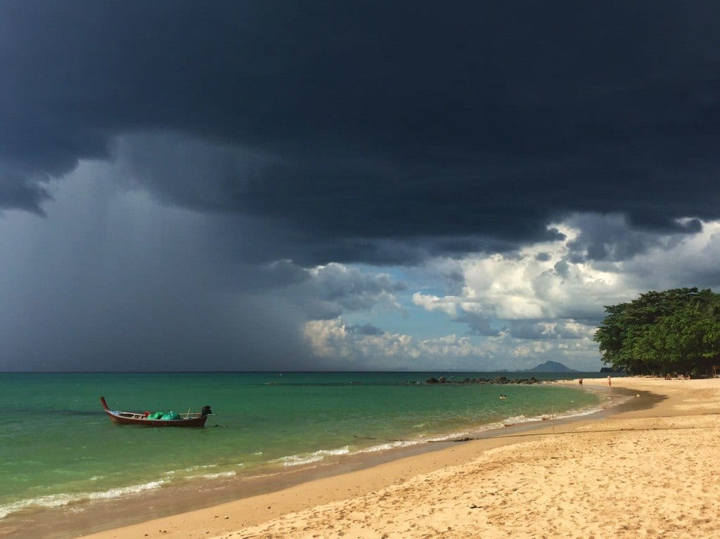 An extremely dark storm cloud over the sunny beach and blue-green water of Koh Lanta.