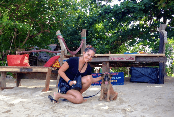 Kate pets a brown puppy named Monroe on a beach in Thailand.