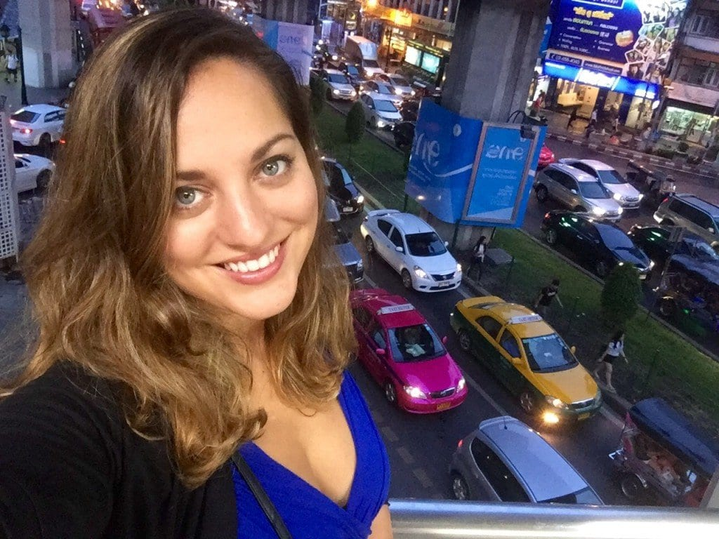 Kate stands in front of a line of cars in Siam Square, Bangkok.