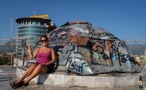 Kate gives a peace sign while sitting in front of a graffiti-covered dome on top of the pyramid in Tirana.