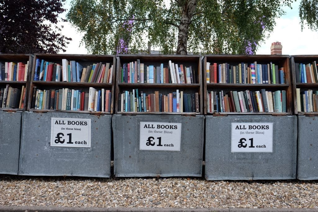 "Rows of used books for sale with a sign labeled ""all books 1 pound"" in Haye on Wye, Wales."