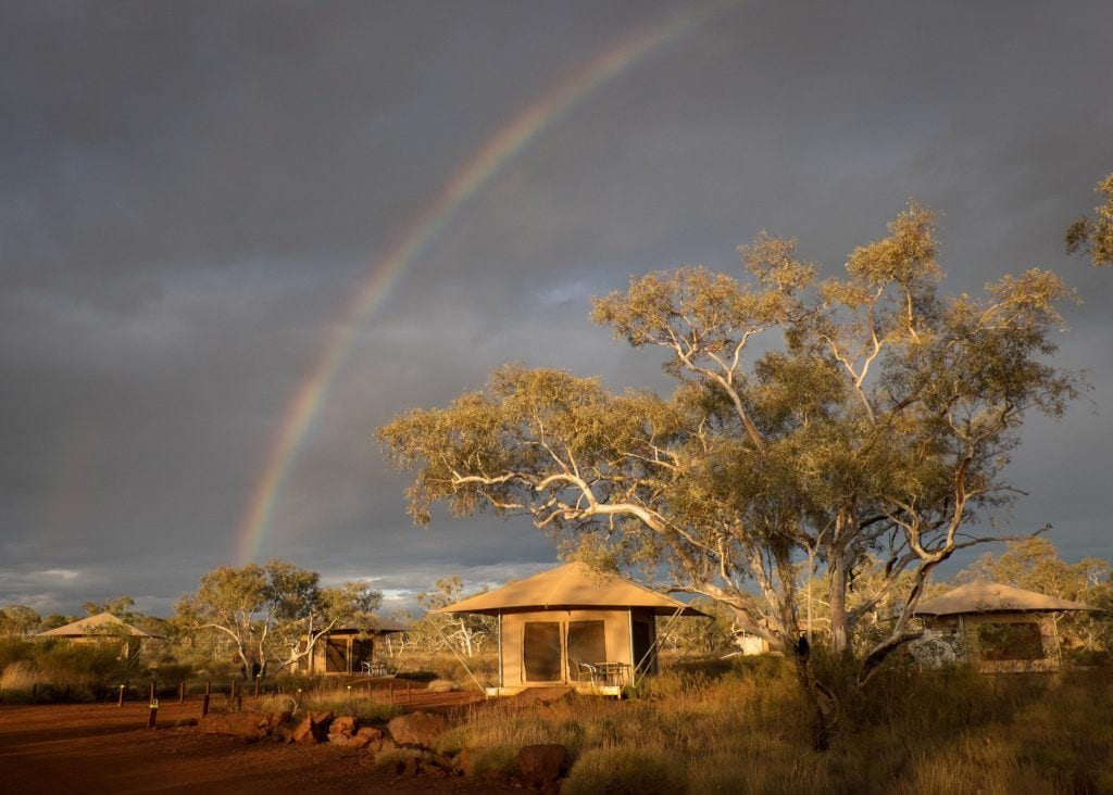 A rainbow over a tent in Karijini National Park, Australia