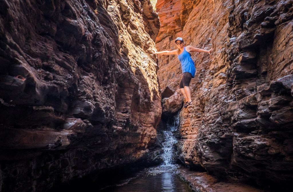 "Kate ""spider-walking"" in a narrow opening in Karijini National Park in Western Australia, holding her body high up wedged between two walls."