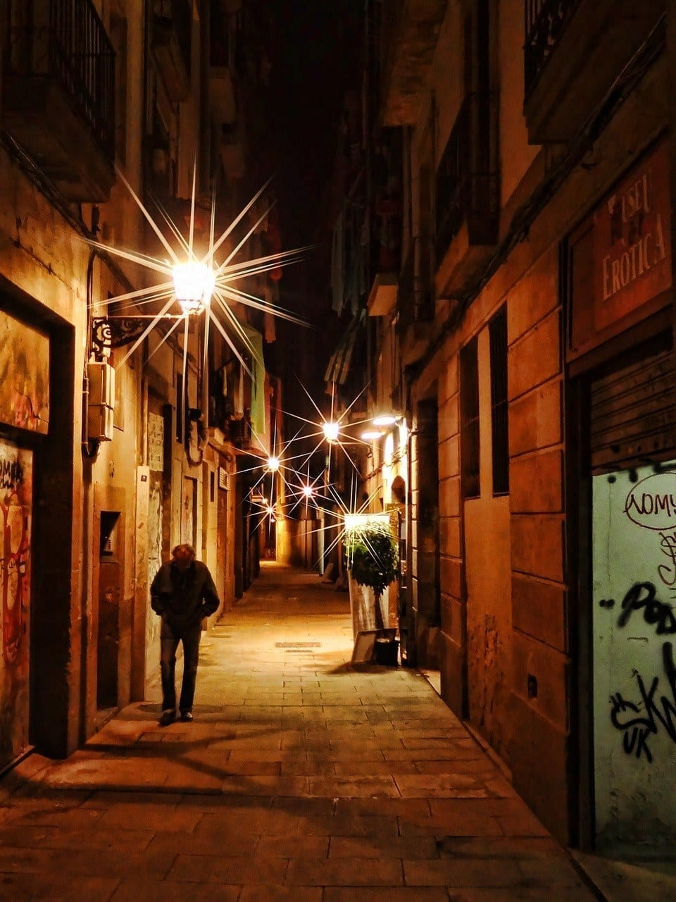 A dark side street in Barcelona; the street lights have points like stars.