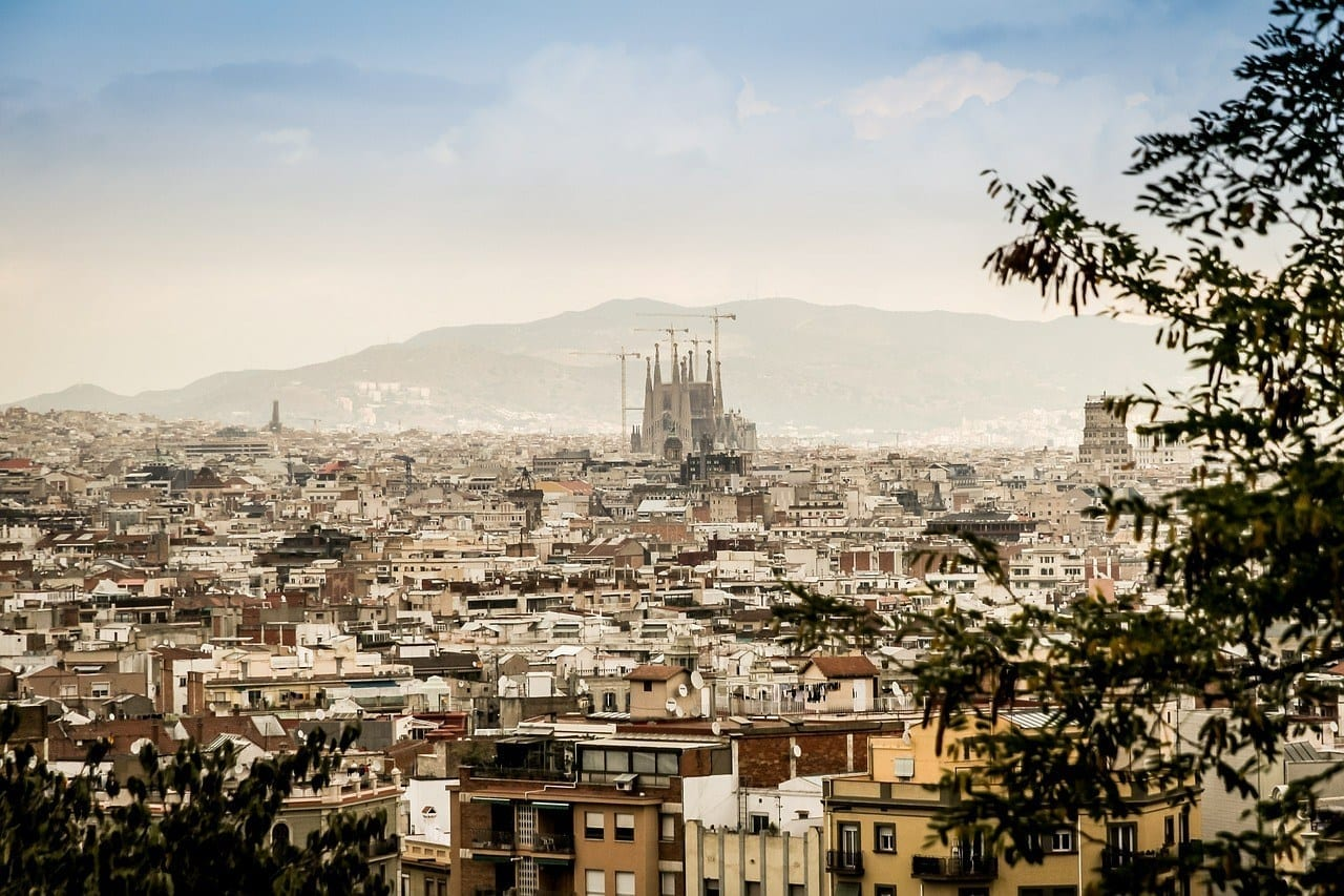 A faded view of Barcelona from above. You see the spires of the Sagrada Familia poking far above the rest of the buildings.