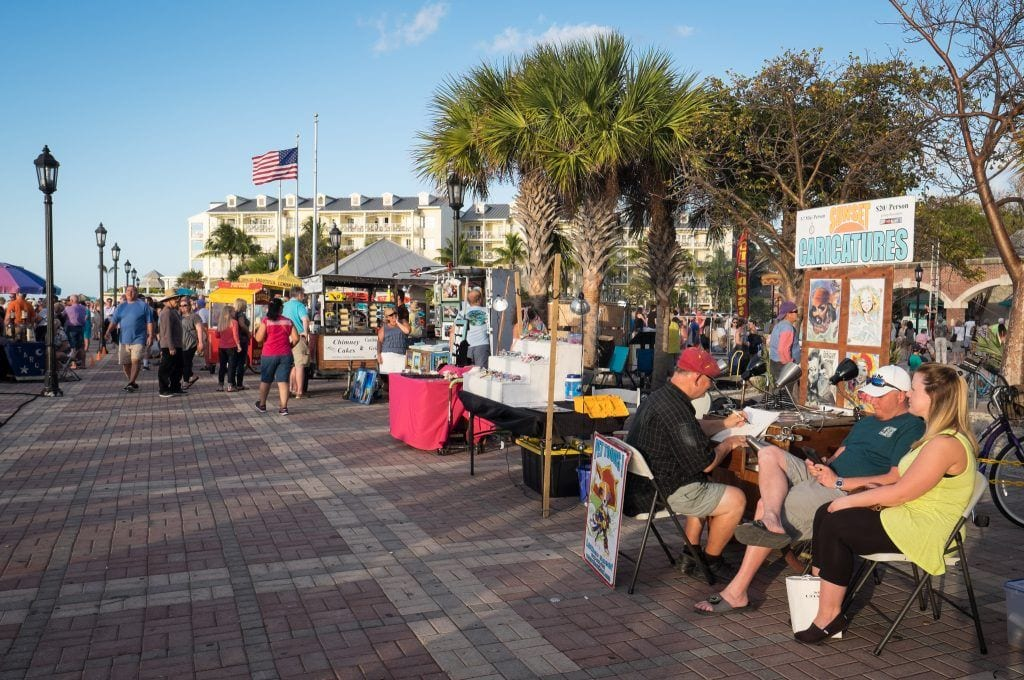 People gathering at outdoor booths for the sunset celebration on the edge of the water in Key West.
