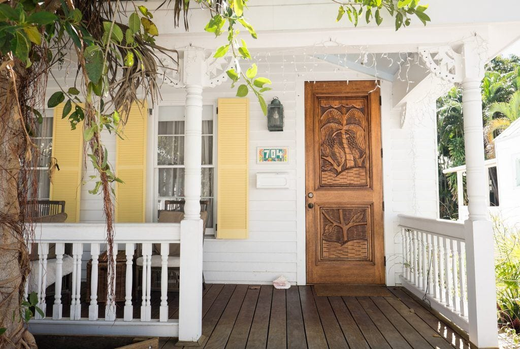 A white cottage with a porch and dark wooden front door in Key West