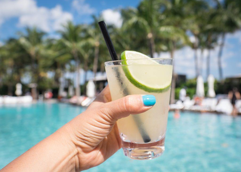 Kate's hand with a bright turquoise painted thumbnail holding a margarita in front of the bright turquoise pool at the W South Beach.