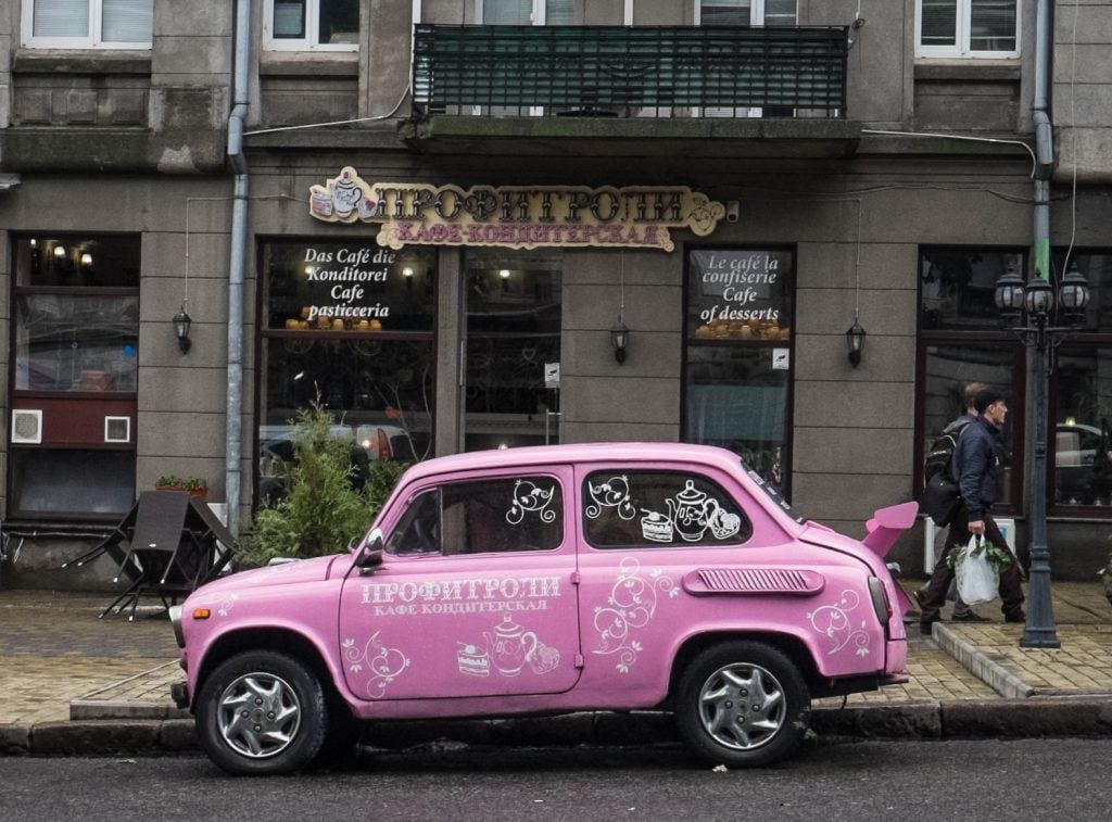 A pink car in front of a gray building in Odessa, Ukraine.