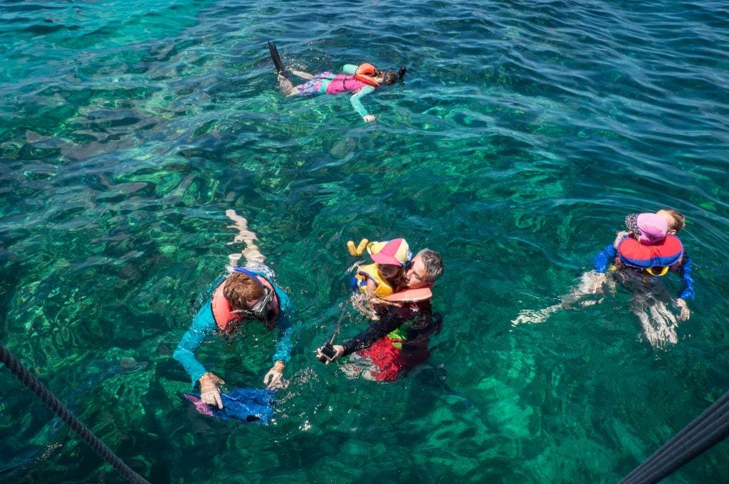 Four snorkelers in the neon teal water at Pennekamp State Park in Key Largo.