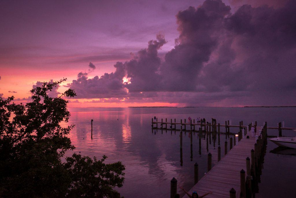 A dramatic pink and purple cloudy sunset over the water in Key Largo.