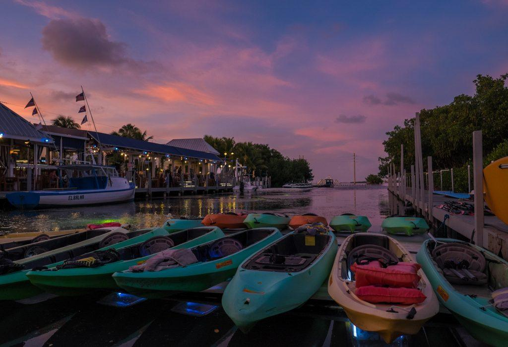 Multicolored kayaks moored on shore at a canal. The sky is a pink, purple and blue sunset.