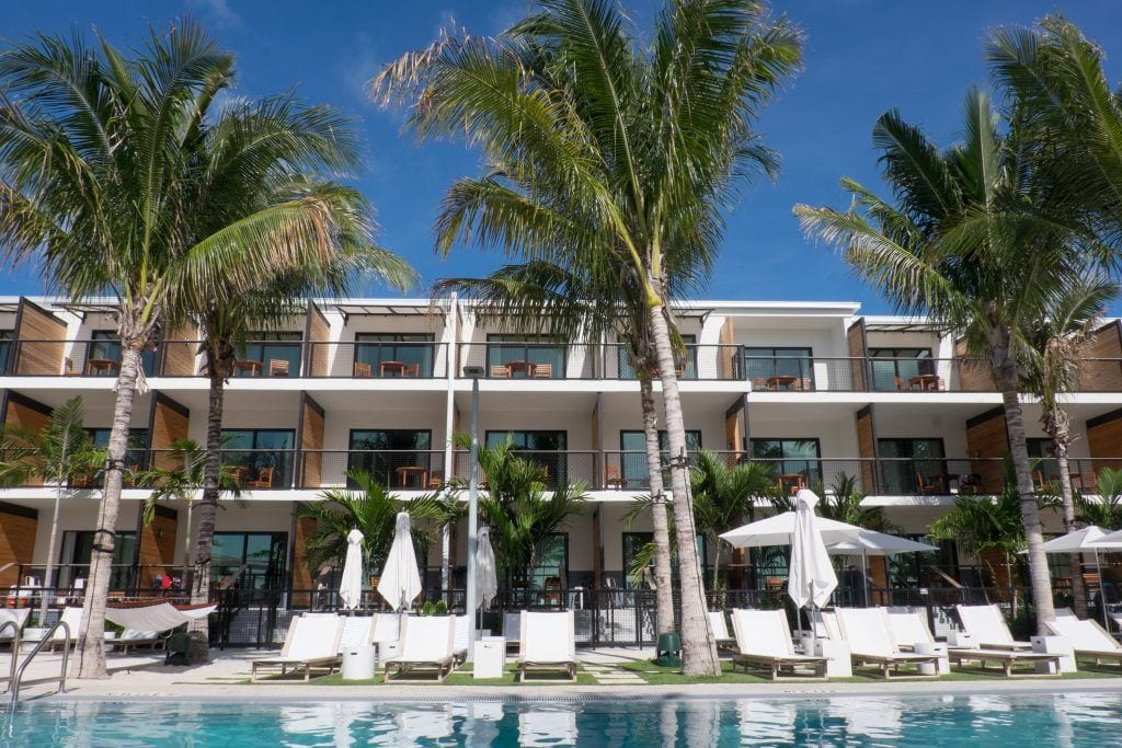 A pool edged with white pool chairs and tall palm trees in front of a bright white modern hotel building.
