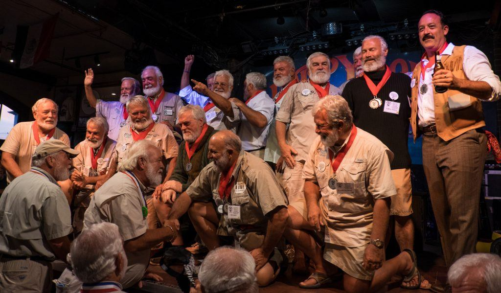 Around 12 Hemingway lookalikes, with white beards, dressed in khaki shorts, on stage at the Hemingway lookalike contest in Key West!